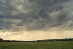 Storm cloud over yellow green fields forests and hills Stock Images