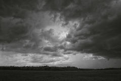 Storm cloud over yellow green fields forests and hills Royalty Free Stock Photo