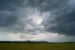 Storm cloud over yellow green fields forests and hills Stock Photography