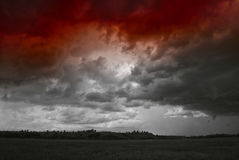 Storm cloud over yellow green fields forests and hills Stock Photo