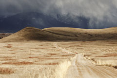 Storm Cloud Passing Through a Barren Mountain Land. A storm cloud is passing over a barren landscape with snow-covered mountains in the background. A dirt road Stock Image