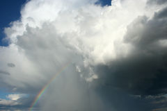 Storm cloud rainbow. A sky scene with storm cloud / clouds / cloudburst, rain / shower and rainbow Stock Image