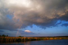 Storm cloud and a rainbow. Summer landscape with a storm cloud and a rainbow over the river Royalty Free Stock Images