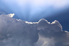 Storm cloud silver lining. Sun rays behind a dark storm cloud gives the appearance of a silver lining Stock Photography