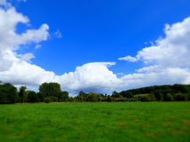 Storm cloud summers day. Farmers field on a summers day with blue sky white clouds approaching storm Royalty Free Stock Image