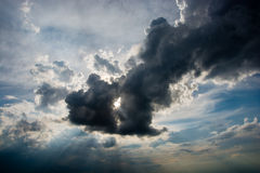 Storm cloud. The sun's rays streaming through the big black storm cloud royalty free stock images