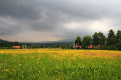Storm clouds. Over the mountains and yellow field Royalty Free Stock Images