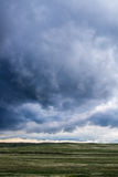 Storm clouds above field of green grass. Storm clouds over prairie meadow field of green grass and rolling hills located in the Colorado eastern plains / Kansas Royalty Free Stock Image