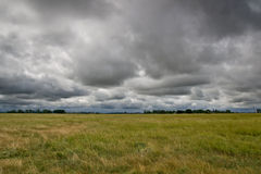 Storm clouds approaching. Over green fields Royalty Free Stock Image