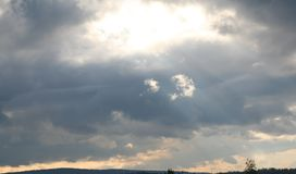 Storm clouds. Beautiful gray-white storm clouds with rays of light Royalty Free Stock Photography