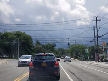 Storm clouds beyond the traffic. NY road on a hot, humid and soon to be stormy summer day stock image