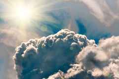 Storm Clouds in the blue sky and sun, background Stock Photos
