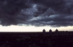 Storm clouds cover the city. Storm front over tall buildings and amid the rivers and forests royalty free stock photography