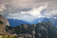 Storm clouds covered Trenta Valley, Julian Alps. The misty Trenta Valley covered with storm clouds with the forested ridge of Velika Ticarica  from Triglav Lakes Stock Photos