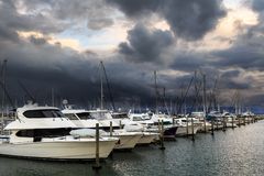 Storm clouds darken the sky over yachts in a marina. Motorboats and sailboats clustered together in the protected waters of a marina, while a storm brews in the royalty free stock images