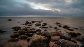 Storm clouds forming over clear sea beach with rocks and clear s. And. dramatic colors royalty free stock photo