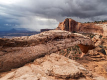 Storm clouds gather in desert. Storms clouds gather and rain begins to fall in the distance in the red rock canyons and Mesa Arch of Canyonlands National Park Stock Photography