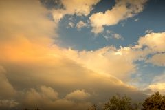 Storm clouds gather on the horizon. Storm clouds abate after a storm as the sun breaks through image with copy space in landscape format royalty free stock photos