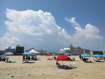 Storm Clouds Gather at Ocean City Maryland. Photo of storm clouds over the beach in ocean city maryland on 8/7/18. Though still sunny these people will soon have stock image