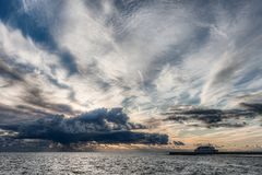 Safe Harbor with stormy sky. Storm clouds gather over the sky while cruise ship arriving to safe harbor Royalty Free Stock Photo