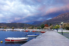 Storm Clouds, Greek Village. Storm clouds building up over a small Greek village and small boats in harbour, Greece, early morning Stock Photo