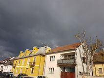 Storm clouds and houses Stock Photos