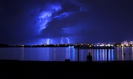 Storm clouds with lightning and a man sitting under a roof on the river bank