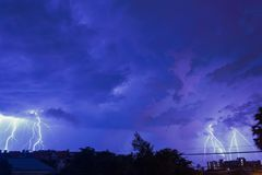 Storm clouds with lightning strike bolts passing over night city Royalty Free Stock Photography