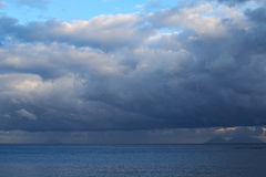 Storm clouds are low over the sea. Mountains in the haze could be seen on the horizon. Marina di Patti. Sicily.  Royalty Free Stock Image