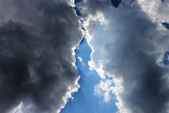 Battle of the clouds. Storm clouds meeting with the sun rays shining through before they merge royalty free stock photos