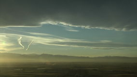 Storm clouds moving over mountain range at sunset stock footage