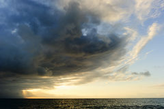 Storm Clouds. Is an ominous storm moving in over the ocean as a bright set of sunrays burst through the darkness to light the way Stock Image