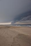 Storm clouds over beach. Scenic view of dark storm clouds over ocean beach Stock Photo