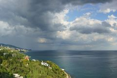 Storm clouds over the blue Black sea in the resort village of Alupka. Cypresses grow on the slope royalty free stock images