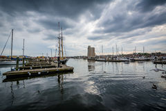 Storm clouds over docks and boats in Harbor East, Baltimore, Mar Royalty Free Stock Photo