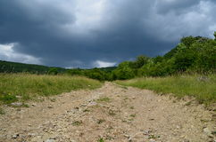 Storm clouds over field road No 3. The path passes through a meadow along the forest meadow royalty free stock images