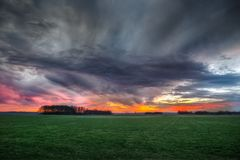 Storm Clouds over Field During Sunset Stock Photo