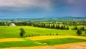 Storm clouds over fields and distant mountains seen from Longstr Stock Photos