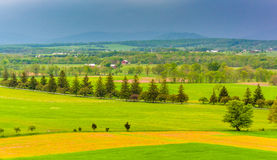 Storm clouds over fields and distant mountains seen from Longstr Stock Photography