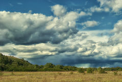 Storm clouds over the fields of the green valley Stock Photo