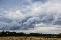 Storm clouds over the forest. Beautiful menacing sky over the field Royalty Free Stock Images