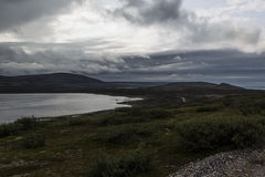 Storm clouds over the green valley and the lake, highlands. Royalty Free Stock Photos