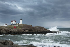 Storm Clouds Over Lighthouse with Waves Crashing. Storm clouds over Nubble lighthouse as waves crash on rocky coast of Maine Royalty Free Stock Images