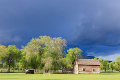 Storm clouds over log cabin. Stock Photography