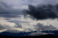 Storm clouds over the mountains. Fagaras mountains in Romania.Storm clouds over mountains covered with snow on peaks stock image