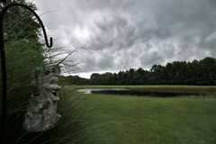 Storm clouds over pond with bird feeder in foreground. Storm clouds over a pond in rural Indiana with a bird feeder in the foreground Stock Photo