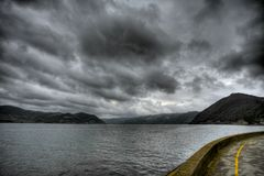Storm clouds over river and mountains - HDR Stock Photography