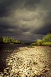 Storm clouds over the river Stock Photos