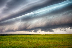 Storm clouds over the sloping field Stock Image