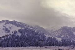 Storm clouds over snow covered mountains. Bighorn mountains of Wyoming USA in the winter with dramatic sky stock photography
